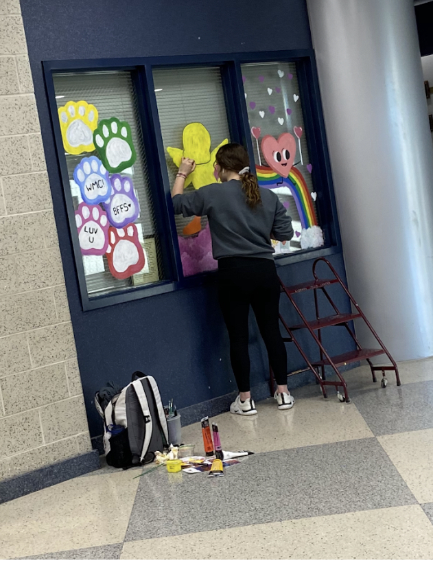 Makenna Lindsey paints the windows for Valentine's Day.
