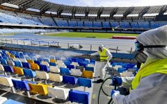 (FILES) In this file photo taken on March 04, 2020 Picture taken on March 4, 2020 shows cleaners wearing a protective suit, as they sanitise the seats of the San Paolo stadium in Naples. - Hiring is surging and wages are rising in the United States as the year begins, but the coronavirus is poised to infect the economy and hamper President Donald Trump's re-election bid. Wall Street has tumbled in recent days as the outbreak spread and undermined the view that the US economy is inoculated against the danger. The White House has tried to downplay the impact, and Trump on march 6, 2020 even made the extraordinary claim that US businesses are benefitting from people staying in the country while predicting stocks would bounce back. (Photo by CIRO FUSCO / ANSA / AFP) / - Italy OUT