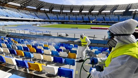 (FILES) In this file photo taken on March 04, 2020 Picture taken on March 4, 2020 shows cleaners wearing a protective suit, as they sanitise the seats of the San Paolo stadium in Naples. - Hiring is surging and wages are rising in the United States as the year begins, but the coronavirus is poised to infect the economy and hamper President Donald Trump