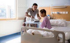 A doctor helps an elderly woman.