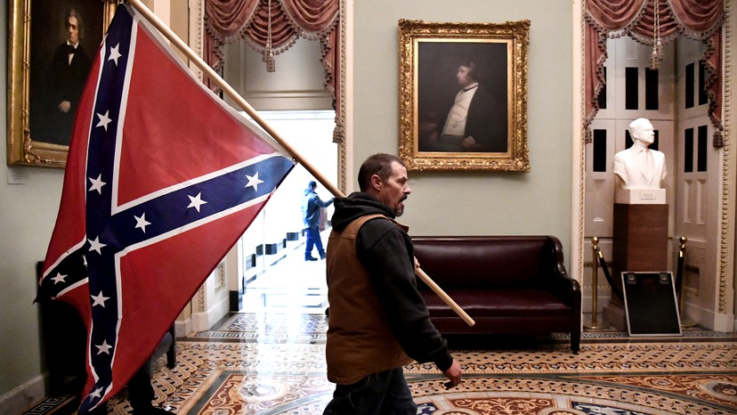 An man carrying a Confederate flag, later identified as Delaware resident Kevin Seefried, walks through the halls of Congress following the storming of the U.S. Capitol Building on January 6, 2021 by supporters of outgoing president Donald Trump. The protesters had hoped to overturn the certification of the 2020 election, but their actions only served to cement the ultimate fate of Trumpism as yet another failed reactionary movement. Photo credits: Mike Theiler/Reuters.