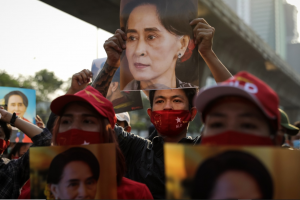 Protesters hold up photos of State Counselor Aung San Suu Kyi, de facto leader of Myanmar, at the embassy in neighboring Thailand. In a bloodless coup, the military of Myanmar—the Tatmadaw—overthrew Aung San Suu Kyi and the civilian government following a decisive loss in the national elections, which it declared fraudulent. The events represent a culmination of Myanmar's fall from grace over the past few years; formerly welcomed as a democratic experiment, the country has since been plagued by ethnic conflict with a systematic genocide against its Rohingya minority. Photo credits: Lauren DeCicca/Getty Images.